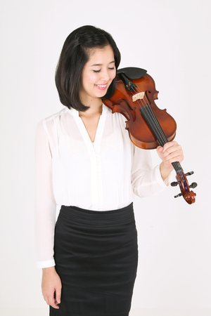 A female violinist holding a violin upside down Stock Photo