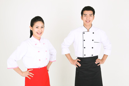 A male cook and a female cook standing with hands on waist Stock Photo