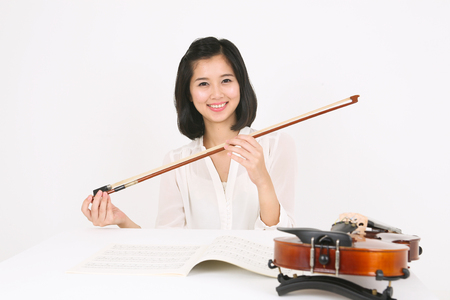 gifted: A female violinist sitting at the desk as holding a violin bow Stock Photo