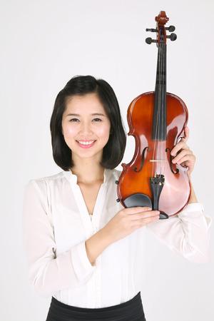 instrumentalist: Chest shot of a female violinist holding a violin upward