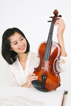 instrumentalist: A female violinist sitting at the desk as holding a violin