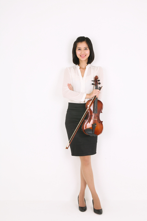 instrumentalist: A female violinist holding a violin and bow as crossing arms Stock Photo