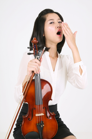 instrumentalist: A female violinist yawning as holding a violin and a bow Stock Photo