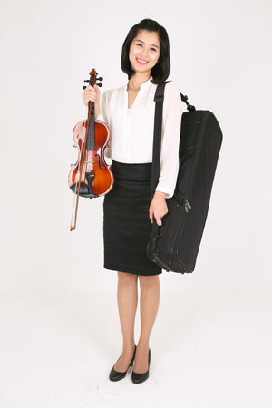 A female violinist holding a violin and a bow as carrying a violin case on shoulder Stock Photo