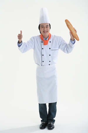 A man holding a loaf of baguette bread