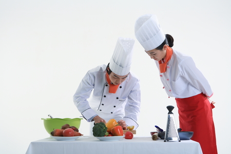 A couple of cooks cooking together Stock Photo