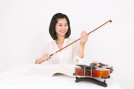 instrumentalist: A female violinist sitting at the desk as holding a violin bow Stock Photo