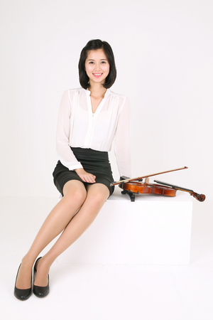 instrumentalist: A female violinist sitting down with a violin laid by side