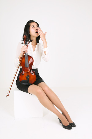 gifted: A female violinist yawning as holding a violin and a bow Stock Photo
