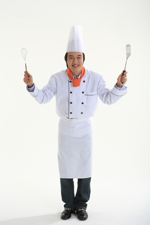 A male cook holding a spatula and eggbeater as standing straight