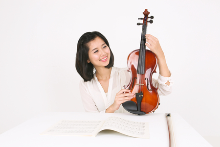 A female violinist sitting at the desk as holding a violin