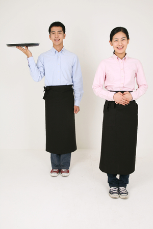 A waiter and a waitress waiting for customers