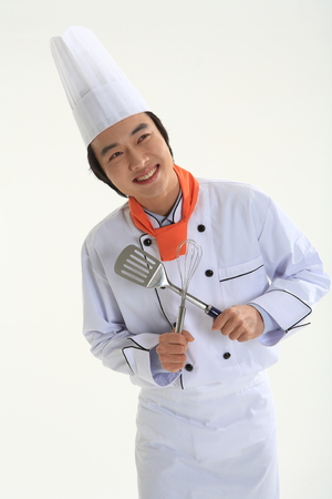 A male cook holding a spatula and eggbeater Stock Photo