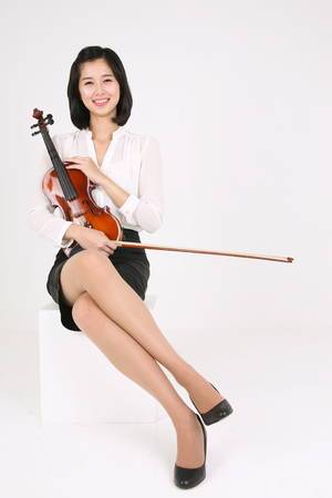 instrumentalist: A female violinist holding a violin and a bow as sitting down