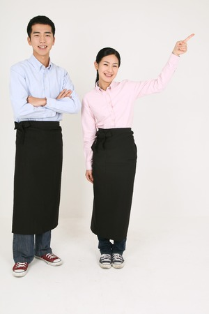 A waiter and a waitress pointing sideway Stock Photo