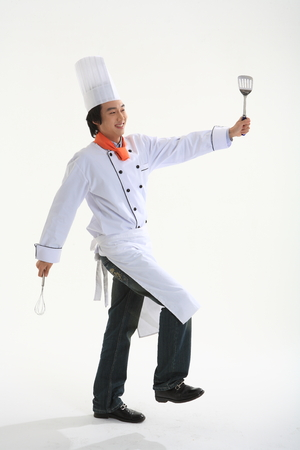 A male cook holding a spatula and eggbeater in running motion
