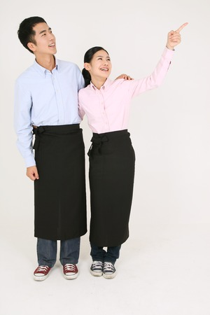 tied in: A waiter and a waitress pointing sideway Stock Photo