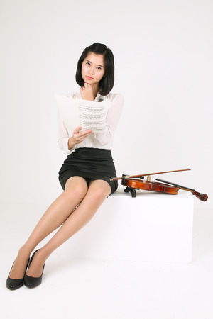 A female violinist reading musical notes with a violin laid by side