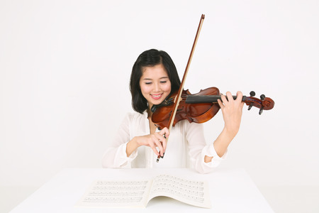 A female violinist playing the violin sitting at desk
