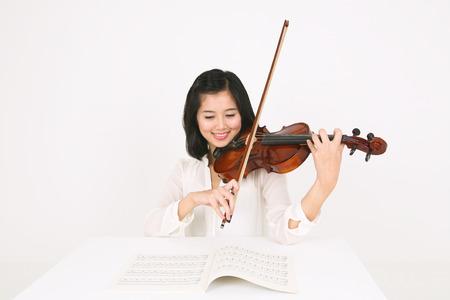 Een vrouwelijke violist die de viool zit aan het bureau Stockfoto