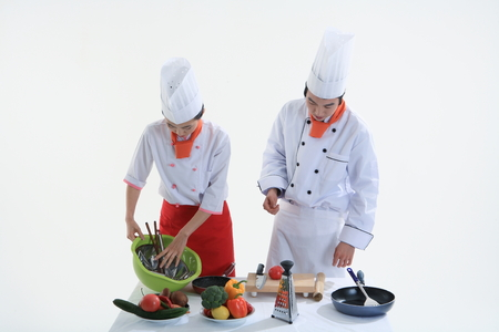 A male cook and a female cook cleaning up after cooking Stock Photo