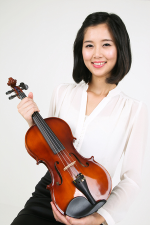 gifted: A female violinist holding a violin body as sitting down