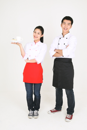 nice body: A male cook and a female cook holding a cup of coffee and a piece of cake