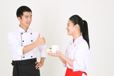A male cook and a female cook holding a cup of coffee and a piece of cake