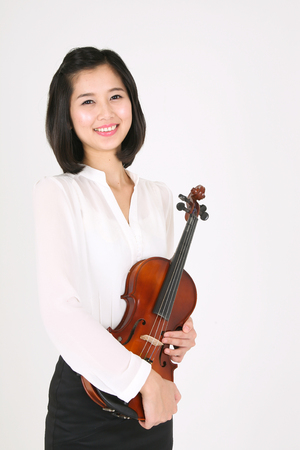 A female violinist holding violin in arms Stock Photo