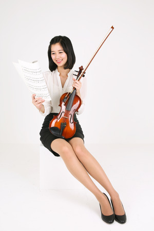 A female violinist holding musical notes Stock Photo