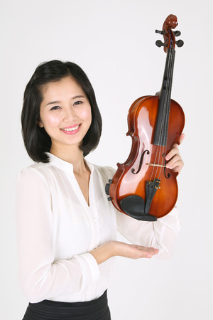 gifted: Chest shot of a female violinist holding a violin upward