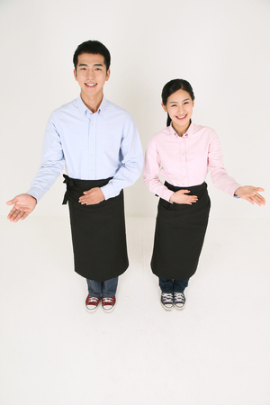 A waiter and a waitress welcoming