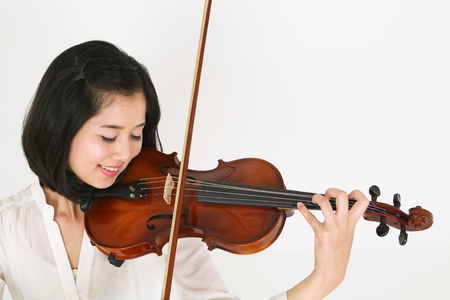 A female violinist playing the violin with eyes closed