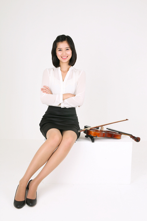 A female violinist sitting down with a violin laid by side