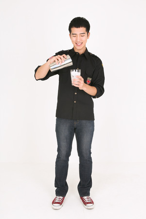 A male bartender making cocktail with a shaker and ice