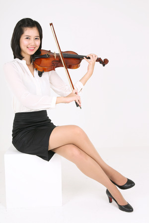 instrumentalist: A female violinist playing the violin as sitting down Stock Photo
