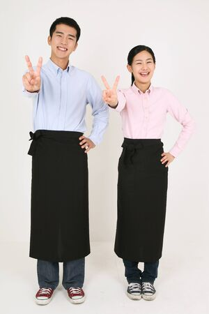 A waiter and a waitress posing with v fingers Stock Photo