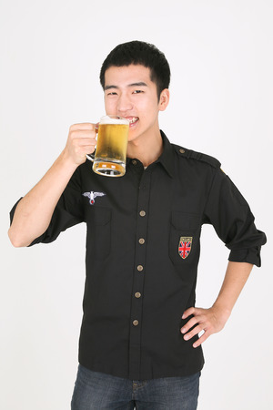 A male bartender holding a glass of beer Banco de Imagens