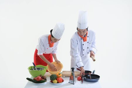A male cook and a female cook cooking together