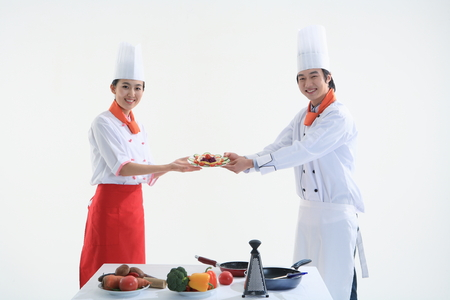 A couple of cooks presenting a plate of salad Stock Photo