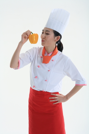 A female cook holding vegetable in hand