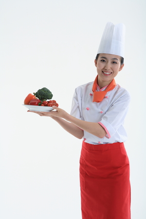 A female cook holding a plate of vegetable