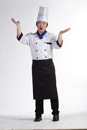 A male cook pretending to weigh with his hands Stock Photo
