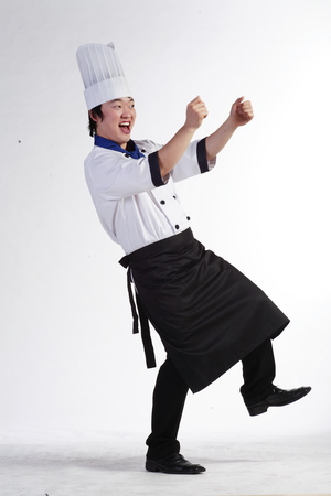 drunken: A male cook dancing with both arms up standing with one leg