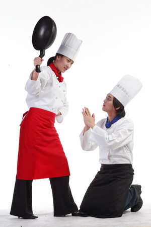 A female cook threatening a male cook with a wok