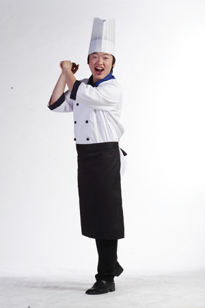 A male cook pretending to hold a bat