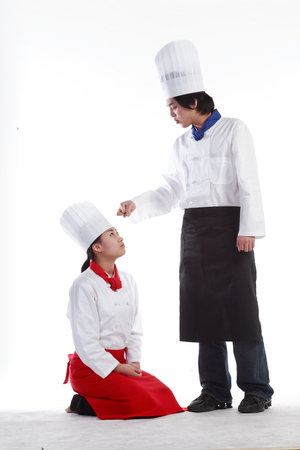 A male cook scolding a female cook as she is kneeling down Stock Photo