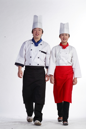 A couple of cooks in walking motion side by side Stock Photo