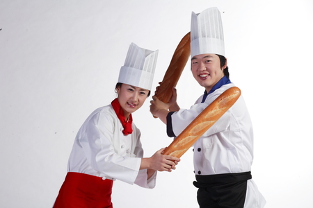 mimo: Close up shot of a couple of cooks pretending to have a sword fight with bread