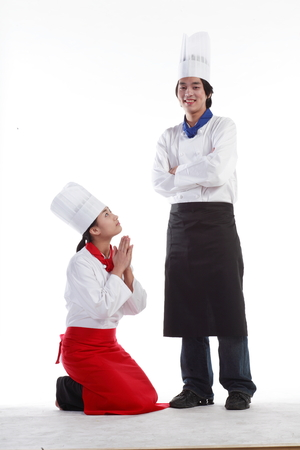 forgiving: A male cook scolding a female cook as she is kneeling down Stock Photo